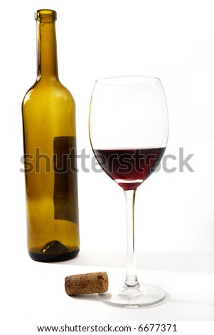 Red vine in a glass and a bottle in front of a white background