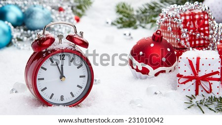 Red vintage alarm clock in the snow  - stock photo