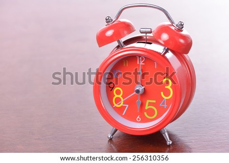 Red vintage alarm clock on wood table - stock photo