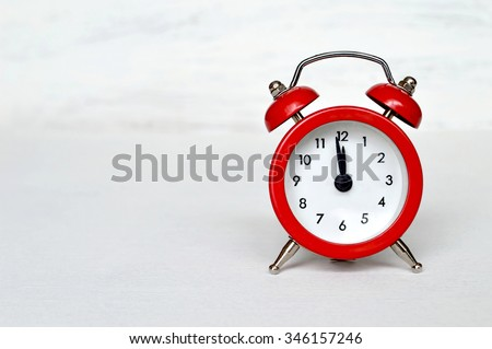 Red vintage alarm clock striking midnight or midday - stock photo