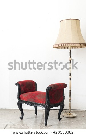 Red vintage armchair and lamp on white wall.