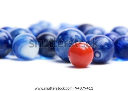 Red vintage marble standing out of a crowd of blue marbles