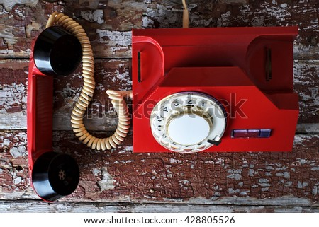 Red vintage phone on wooden background with pencil and glasses close-up, top view, pick up the phone - stock photo