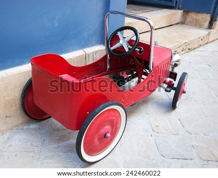 Red vintage toy car near entrance to the house. Back and side view. - stock photo