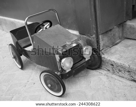 Red vintage toy car near entrance to the house. Front and side view. Aged photo. Black and white. - stock photo