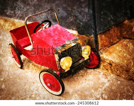 Red vintage toy car near entrance to the house. Front view. Retro aged photo with scratches. - stock photo