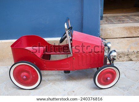 Red vintage toy car near entrance to the house. Side view. - stock photo