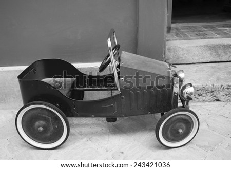 Red vintage toy car near entrance to the house. Side view. Aged photo. Black and white. - stock photo
