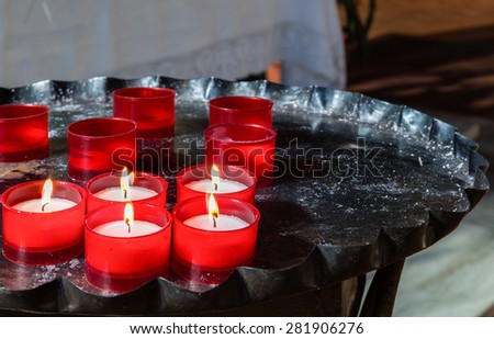 red votive candles arranged on old black iron candlestick, some still burning