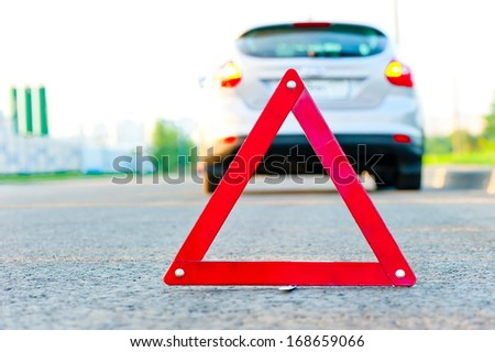 red warning triangle and a car with the emergency alarm - stock photo