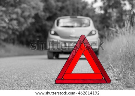 Red warning triangle and green broken car on the road - black and white concept