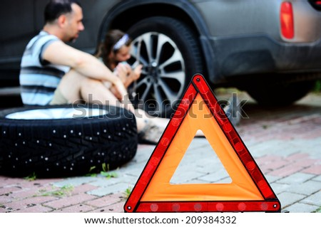 Red warning triangle sign on the road while father and young daughter changing wheel on the road  - stock photo
