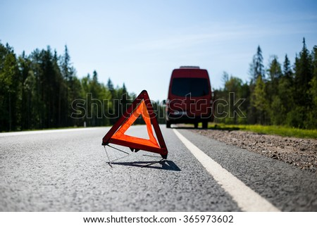 Red warning triangle with a broken down minibus car - stock photo