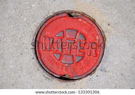 Red water main cover on street - stock photo