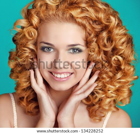Red Wavy Hair. Healthy Curly Hair. Beautiful happy smiling girl portrait  over blue - stock photo