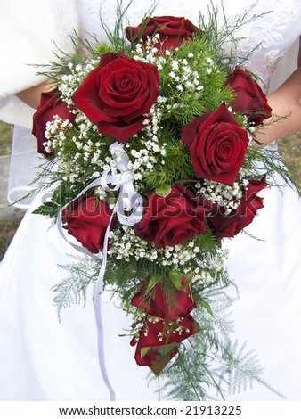 Red wedding bouquet at bride's hands - stock photo