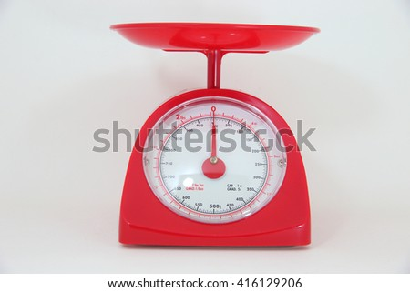 Red weighing machine in white background