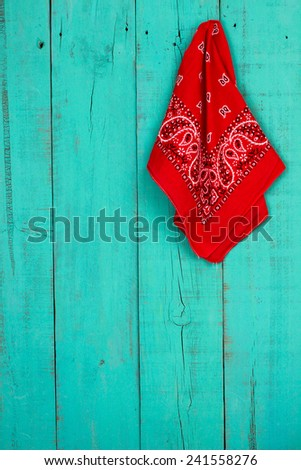 Red western bandana or handkerchief hanging on blank antique rustic teal blue old weathered background; bandanna - stock photo