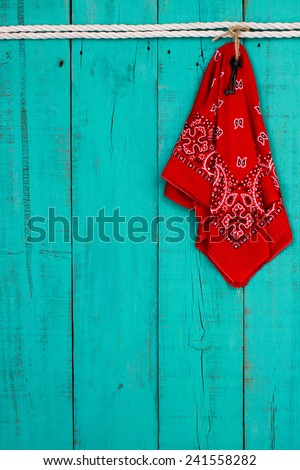 Red western bandanna or handkerchief and black iron key hanging on blank antique teal blue shabby wooden background with white rope border - stock photo