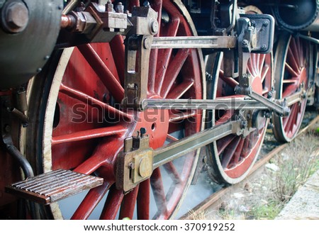 Red wheels of big old steam locomotive. - stock photo