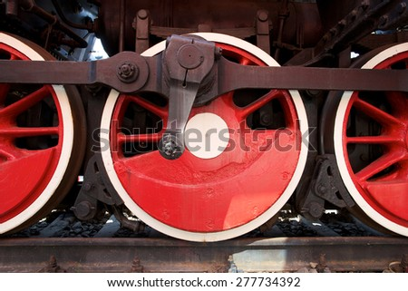 Red wheels of steam locomotive - stock photo