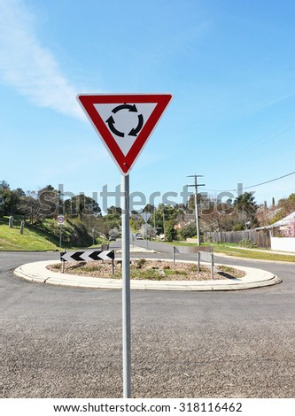 red, white and black sign indicating a roundabout ahead