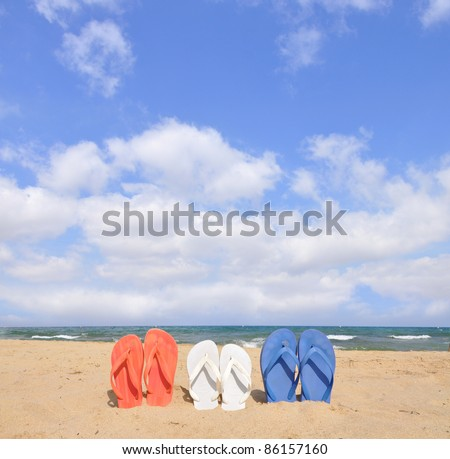 Red White and Blue Flip Flop Sandals on Sunny Beach Blue Cloud Sky - stock photo