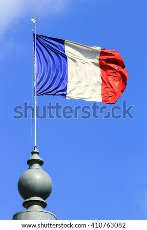 Red, white and blue french flag waving on top of a building in Paris