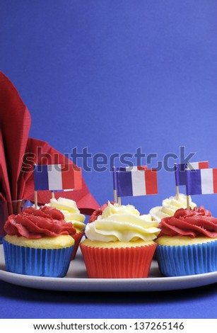 Red, white and blue mini cupcake cakes with flags of France and fleur-de-lis napkin for National holidays of France, Bastille Day, the Fourteenth of July. Vertical with copy space for your text here. - stock photo
