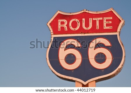 Red, white, and blue Route 66 neon sign in the shape of a US Highway shield glowing without the neon at sunset - stock photo