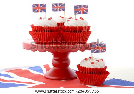 Red white and blue theme cupcakes on red cake stand with UK Union Jack flags on white wood table for Queens Birthday and Great Britain party food.  - stock photo