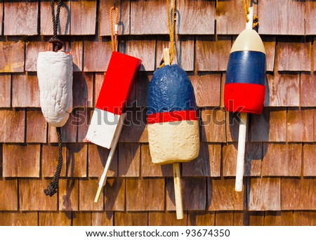 Red white and blue vintage fishing buoys hanging on wood shingled wall - stock photo