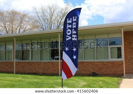 Red white and blue Vote Here sign stands outside polling place at a local school on election day.  - stock photo