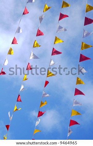 red, white and yellow flags in the street - stock photo