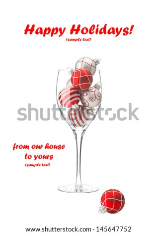 Red & white Christmas balls in wine glass isolated on white with copy space.  - stock photo