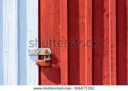 red white door closed by padlock background - stock photo