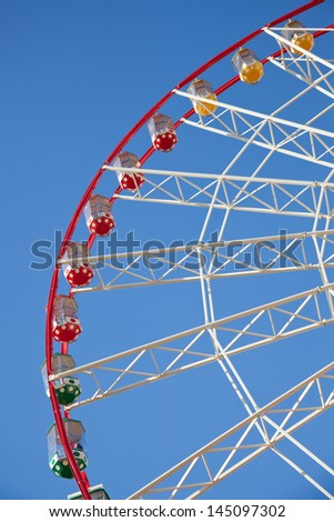 Red, white, green and yellow colorful gondolas of Big Ferris Wheel at amusement park. Clear blue sky on the background.