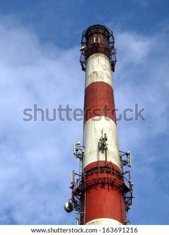 red-white high concrete chimney outlet of heat against a slightly cloudy sky - stock photo