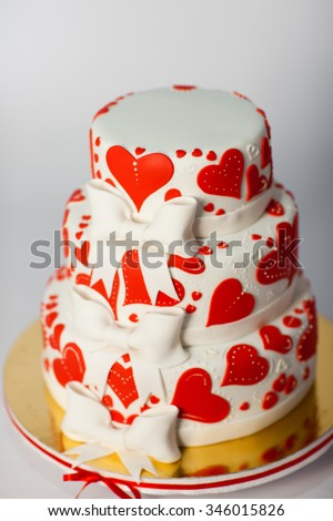Red White three-tiered wedding cake on a white background. - stock photo