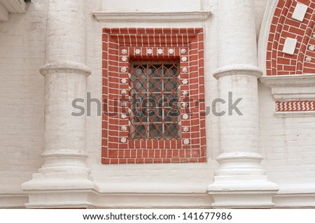 red window on the white bricks building