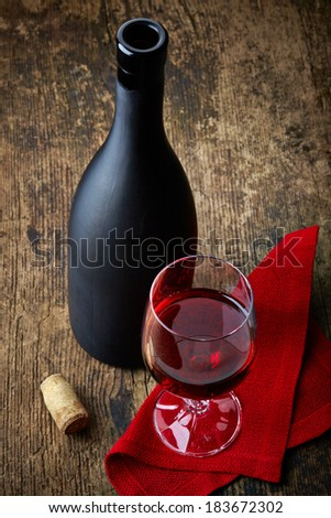 red wine and black bottle on old wooden table - stock photo