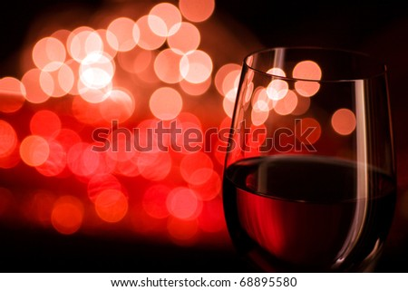 Red wine and blurred lights Shallow depth of field, focus is on the frontal glass line and lamp reflex only. - stock photo