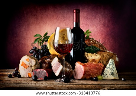 Red wine and different food on a wooden table - stock photo
