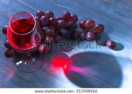 red wine and grape on old wooden table, focus on glass