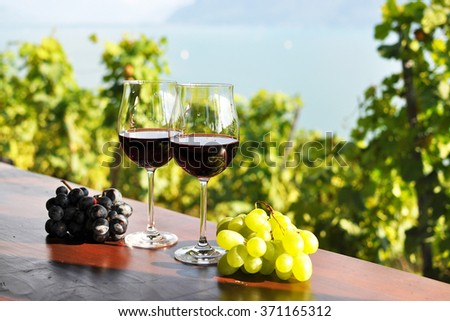 Red wine and grapes against vineyards in Lavaux region, Switzerland