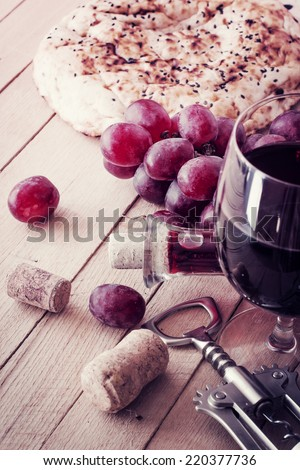 Red wine and grapes in vintage setting - stock photo