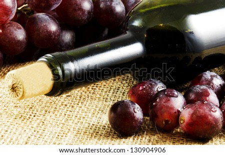 Red wine and grapes on a jute texture - stock photo