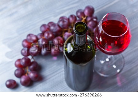 red wine and grapes on old wooden table - stock photo