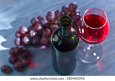red wine and grapes on old wooden table, selective focus