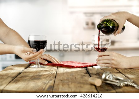 red wine and hands of woman and kitchen room